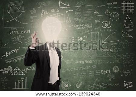 Smart teacher with lightbulb head in class - stock photo