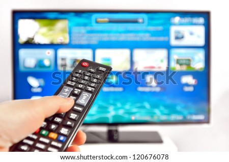 Smart tv and  hand pressing remote control - stock photo
