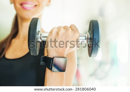Smart watch app template: exercising woman in gym with wearable device - stock photo