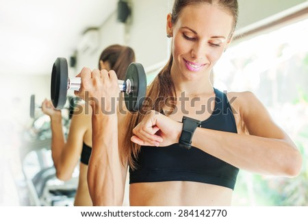 Smart watch showing a heart rate of exercising woman in gym - stock photo