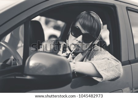 smart woman in a car  doing makeup while standing in  traffic jam