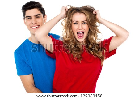 Smart young boy holding his girl from behind while she screams in fun. - stock photo