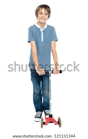 Smart young boy posing with his push scooter. Isolated against white background. - stock photo