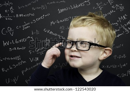Smart young boy wearing a navy blue jumper and glasses stood in front of a blackboard with scientific formulas and equations written in chalk
