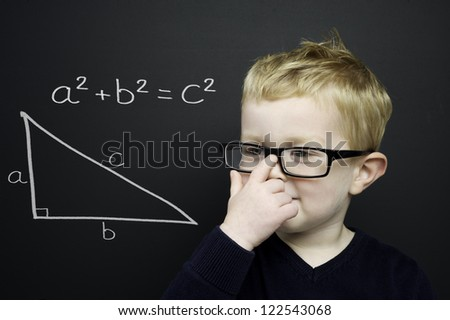 Smart young boy wearing a navy blue jumper and glasses stood in front of a blackboard with the Pythagoras rule explained drawn in chalk - stock photo