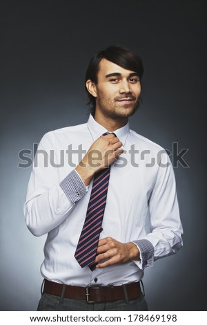 Smart young businessman adjusting his necktie looking at camera smiling. Mixed race male model getting ready for office against black background - stock photo