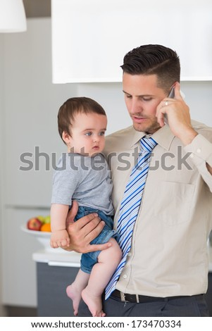 Smart young businessman carrying baby boy while using mobile phone in kitchen - stock photo