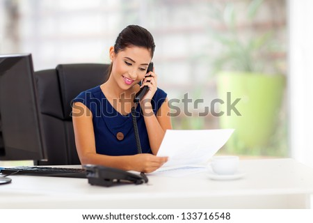 smart young businesswoman on the telephone and reading report - stock photo