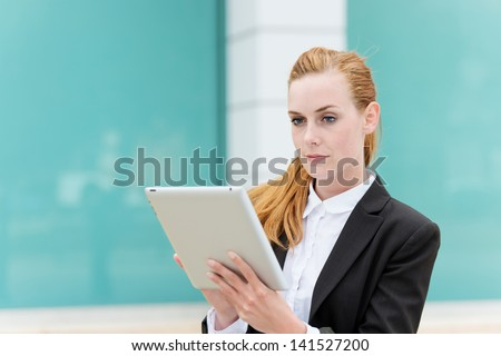 Smart young businesswoman using digital tablet outside - stock photo
