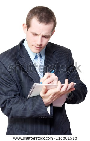 Smart young male personal assistant setting appointments in a handheld diary as he schedules meetings for his boss isolated on white background - stock photo