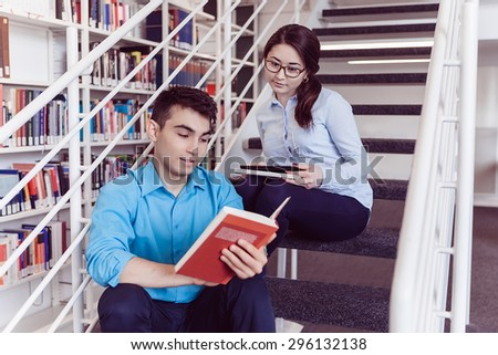 Smart young man and woman reading book together while sitting om stairs in the library
