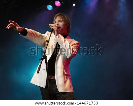 Smart young man singing into microphone on stage