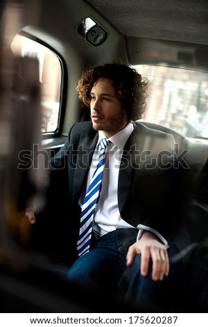 Smart young relaxed businessman traveling in taxi cab
