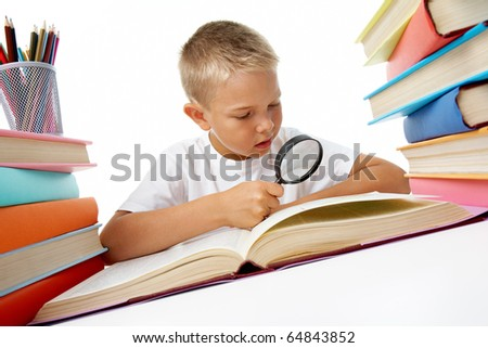 Smart youth looking through magnifying glass while reading open book before him