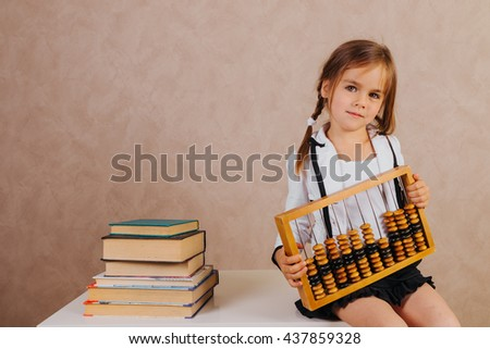 Smartest smart and beautiful little schoolgirl in school uniform with textbooks at school - stock photo