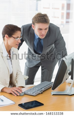 Smartly dressed business couple using computer at office desk