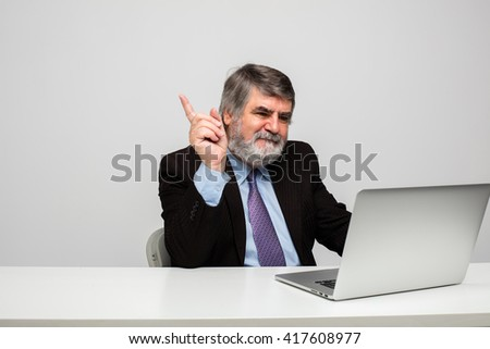Smartly dressed older man using a laptop on a white table.