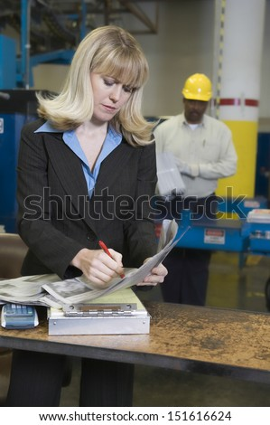 Smartly dressed woman with worker in background at newspaper factory - stock photo