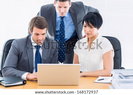 Smartly dressed young colleagues using laptop at office desk