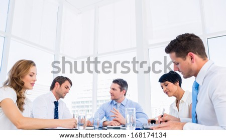 Smartly dressed young executives sitting around conference table in office - stock photo