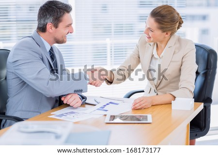 Smartly dressed young man and woman shaking hands in a business meeting at office desk