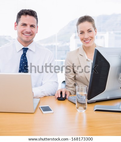 Smartly dressed young man and woman using computer and laptop at office desk