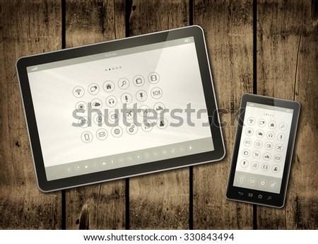 Smartphone and digital tablet PC with desktop icons on a dark wood table - horizontal office mockup - stock photo