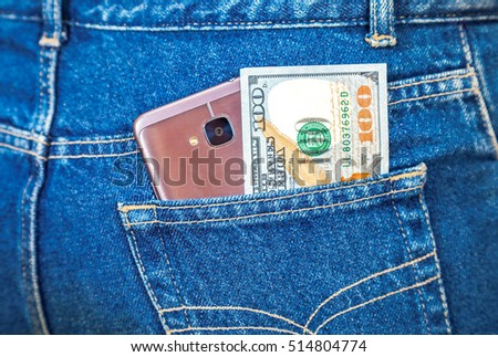 Smartphone and Euro banknote sticking out of the blue jeans pocket