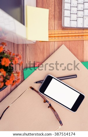 Smartphone and eye glasses on paper by computer in office - stock photo