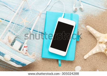 Smartphone and notepad on sea sand with starfish and toy boat. Top view with copy space - stock photo