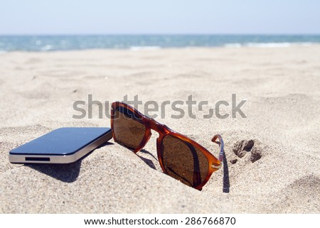 Smartphone and sunglasses on the beach sand - stock photo