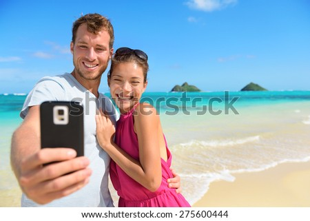 Smartphone - beach vacation couple taking selfie photograph using smartphone having fun holding smart phone camera on Lanikai beach, Oahu Hawaii, USA with Mokulua Islands. Young Asian Caucasian couple - stock photo