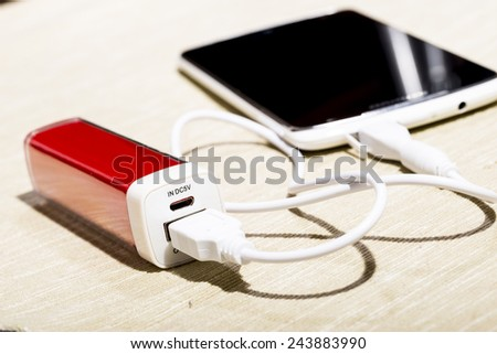 Smartphone charged by power-bank. - stock photo