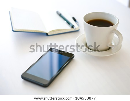 Smartphone close-up, coffee and planning book on the background