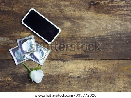smartphone. condoms. White flower. top view, space for text - stock photo