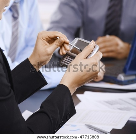 Smartphone handheld in closeup, colleagues working in background.