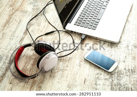 Smartphone, Headphones and Laptop on a wooden Desktop.
