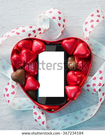 Smartphone in box with chocolates hearts. Gift on Valentine's day, romantic celebration. View from above - stock photo