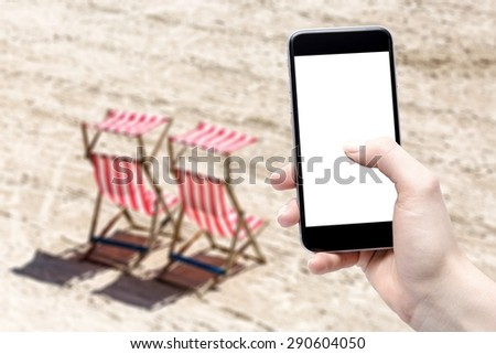 smartphone in hand and beach - stock photo