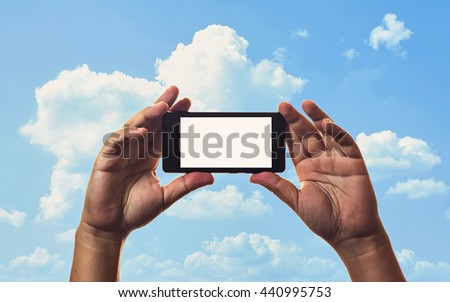 smartphone in hand and blue sky background