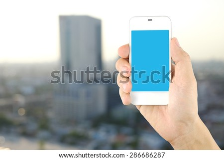 smartphone in hand with city background template for putting word or icon for your design