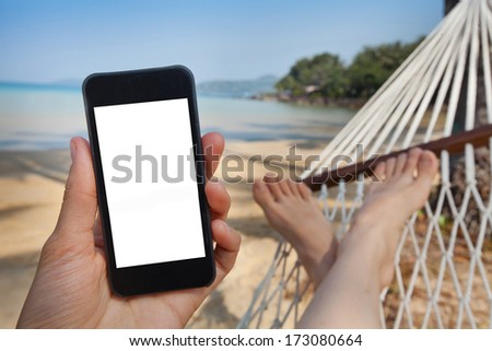 smartphone in the hand in beach hammock - stock photo