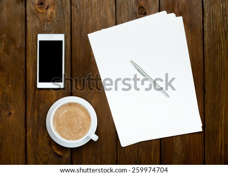 Smartphone, latte coffee and blank paper sheets with a pen on wooden table