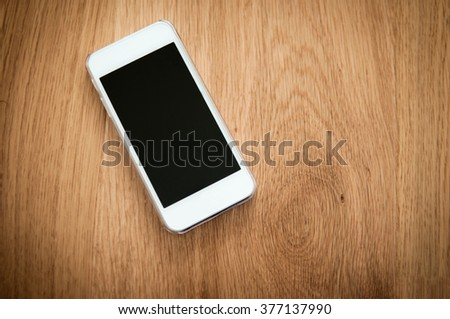 Smartphone laying on a wooden background - stock photo