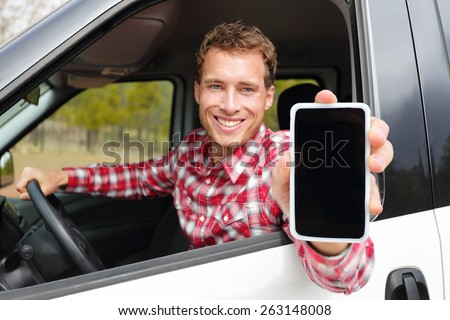 Smartphone man driving car showing app on screen display smiling happy. Male taxi driver using 4g apps showing blank empty touchscreen for gps location. Focus on model and on screen for copy space. - stock photo
