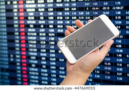 Smartphone on hand with stock market number background  - stock photo