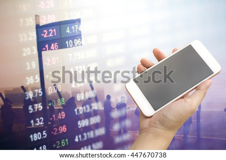 Smartphone on hand with stock market number overlay on silhouette people meeting. - stock photo