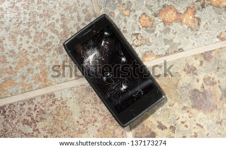 Smartphone on hard floor with cracked screen.