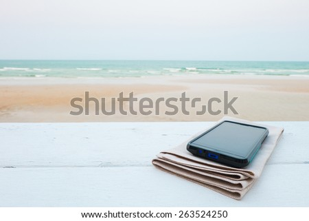smartphone on the beach in summer time - stock photo