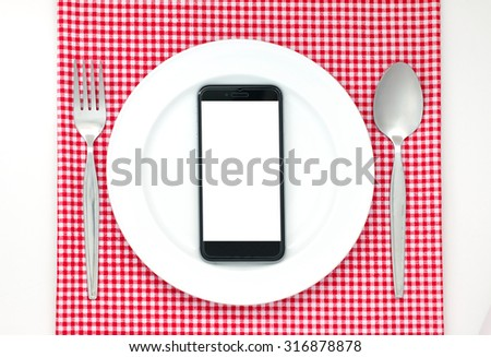 Smartphone on white dish or plate between spoon, fork on red classic checkered tablecloth texture on white table with copy space for advertise food product and other - stock photo